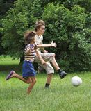 Boys play with boll. Two boys play with boll on the green grass Royalty Free Stock Photos