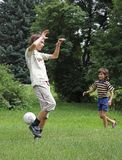 Boys play with boll. Two boys play with boll on the green grass Stock Image