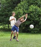 Boys play with boll. Two boys play with boll on the green grass Royalty Free Stock Image