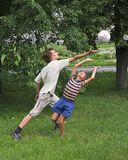 Boys play with boll. Two boys play with boll on the green grass Stock Photos