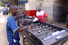 Boys Play Foosball in Dakar. Senegalese boys play with a sidewalk Foosball table in Dakar on their Tabaski holiday (Muslim festival of Eid-al-Adha Stock Photography