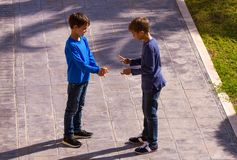 Boys play game rock paper scissor on sunny day in the yard stock photography