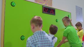 Group of children play a game of reaction speed in scientific museum. The boys play in the game in scientific museum. They pushes buttons on green wall and stock video footage