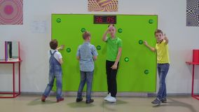 Four boys checks their speed reaction with game in scientific museum. The boys play in the game in scientific museum. They pushes buttons on green wall and stock footage