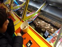 Boys play a penny falls game in an amusement arcade stock video