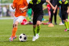 Boys play soccer football match. Training and football match between youth soccer teams. Young boys playing soccer game Royalty Free Stock Photography