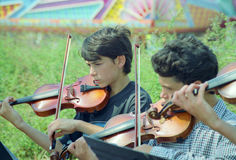 Boys play violin on. Sail 95 Royalty Free Stock Images
