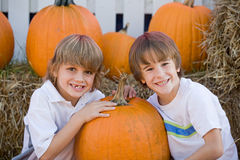 Boys Playing. Two Boys Smiling in a Pumpkin Patch royalty free stock image