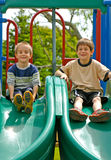 Boys Playing. Two Boys Playing on a double slide Royalty Free Stock Photo