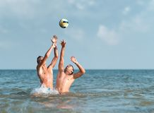 Boys playing with a ball in water Royalty Free Stock Image