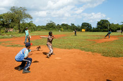 Boys playing baseball on a field at Las Galeras Stock Image