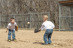 Boys playing catch. Two young boys standing on the baseball field, playing catch Royalty Free Stock Image