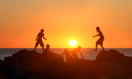Boys playing on the beach. At sunset Stock Image