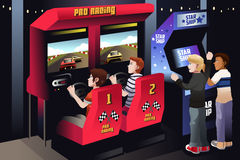 Boys playing car racing in an arcade Stock Photo