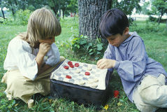 Boys playing checkers in Historical Revolutionary War reenactment, Continental Army camp followers Stock Photos