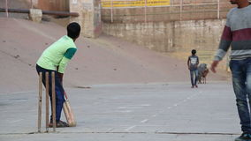 Boys playing cricket on playground in Varanasi, with dogs in background. VARANASI, INDIA - 20 FEBRUARY 2015: Boys playing cricket on playground in Varanasi stock video footage