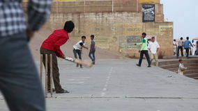 Boys playing cricket on playground in Varanasi, with people passing by. VARANASI, INDIA - 20 FEBRUARY 2015: Boys playing cricket on playground in Varanasi, with stock video footage