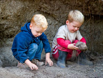 Boys playing with dirt. Two boys playing in the dirt royalty free stock image
