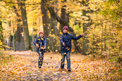 Boys playing with fallen leaves in a park. Autumn in Poland. Stock Image