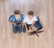 Boys playing with flying helicopter model at home using remote control Stock Photography
