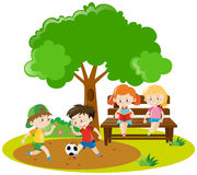 Boys playing football and girls reading in park Royalty Free Stock Photography