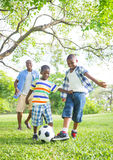 Boys Playing Football in The Park Stock Photo