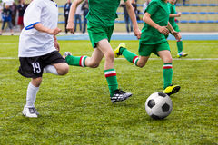 Boys playing football soccer game on sports field Stock Photos