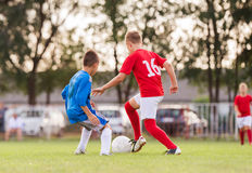 Boys playing football soccer game on sports field Stock Photography