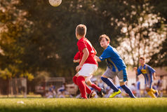 Boys playing football soccer game on sports field Royalty Free Stock Images