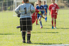 Boys playing football soccer game on sports field Stock Image