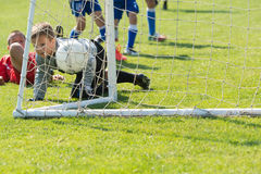 Boys playing football soccer game on sports field Stock Images