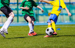 Boys playing football soccer match game. Young boys playing football soccer game. Running players in green and yellow uniforms Stock Photography