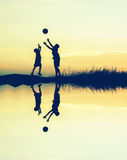 boys playing football at sunset with water reflection. silhouett Stock Photo