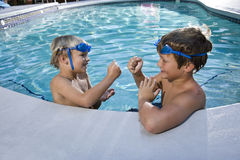 Boys playing games at edge of swimming pool. Two boys playing game of rock, scissors, paper in swimming pool, 7 and 9 years Stock Photos