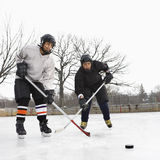 Boys playing ice hockey. Two boys in ice hockey uniforms playing hockey on ice rink Stock Image