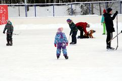 Boys playing ice hockey, and girls are skating on the outdoor rink. stock photography