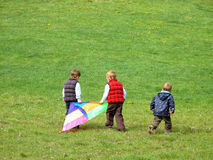 Boys playing with kite. Three boys run up hill with kite on green grass meadow Stock Photography