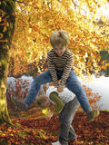 Boys playing leapfrog near lake in autumn Stock Images