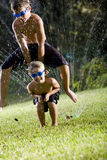 Boys playing leapfrog over lawn sprinkler Stock Image