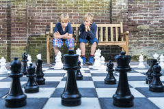Boys playing outdoor chess. Two boys, sitting on a wooden bench, concentratedly thinking about their next move during an outdoors chess game with life sized royalty free stock photos