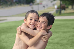 Boys Playing Outside. In the Water Hugging Stock Images
