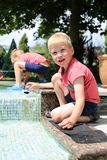 Boys playing with the plastic ducks by the pool Stock Photos