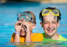 Boys playing in the pool. Boys or brothers playing in the swimming pool Stock Image