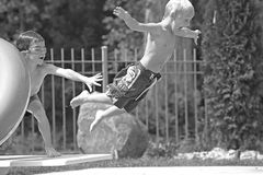 Boys Playing in the Pool. Jumping off the Diving Board Royalty Free Stock Photo
