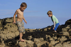 Boys playing on rocks at the seaside. Two young brothers exploring rocks on their holidays near Killybegs in the West of Ireland on a very hot, Summer's day with Stock Photography
