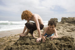 Boys Playing In Sand At Beach Stock Image
