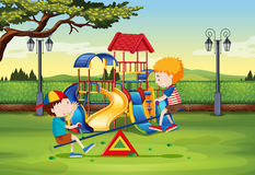 Boys playing on seesaw in the park Stock Photography