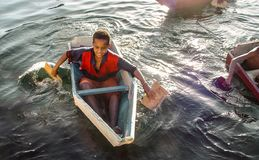 EGYPT: boys plyaing in a selfmade boat on the Nile. Boys playing in selfmade boats on the river Nile Egypt Royalty Free Stock Photo