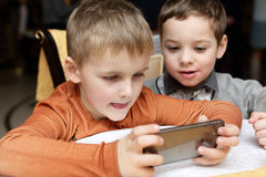 Boys playing in smartphone Stock Images