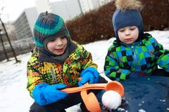 Boys playing with snowball maker. At playground Royalty Free Stock Photos